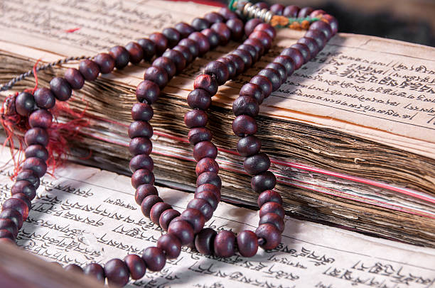 buddhist religious japa mala on manuscript - mahroch stock pictures, royalty-free photos & images