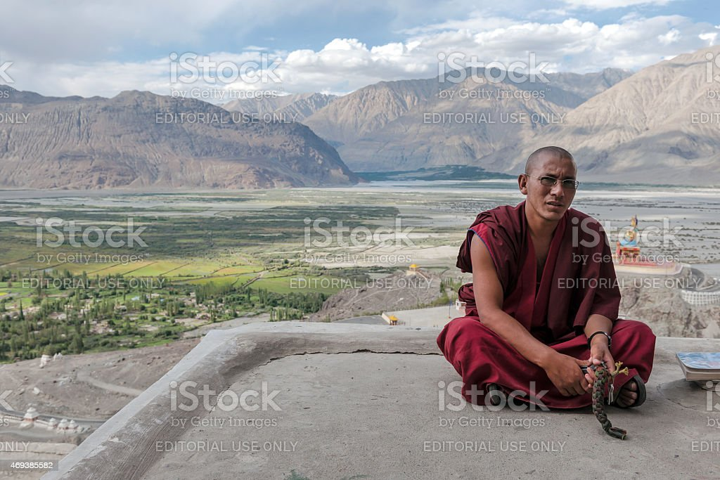 Buddhist sitting and looking curiously  in Diskit Gompa, India Asia stock photo