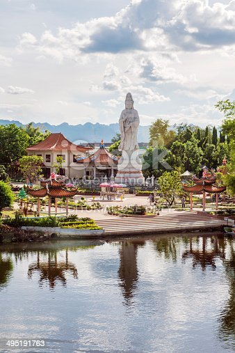 Kanchanaburi, Thailand - May 11, 2014: Along the River Kwai towers a Buddhist statue and several traditional style buildings that stand out against the green trees and mountain scenery in the background.