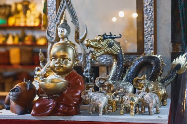 buddhistische statuetten und souvenirs auf dem nachtmarkt - buddha figuren kaufen stock-fotos und bilder