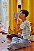 A young Buddhist sits and reads from a religious book in Shwedagon Pagoda temple complex - Yangon, Myanmar