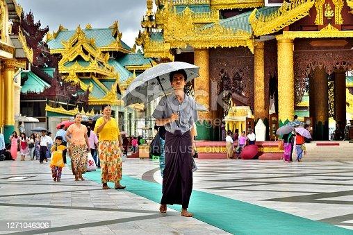An Asian man walks with umbrella on path in traditional golden Shwedagon Pagoda temple complex - Yangon, Myanmar