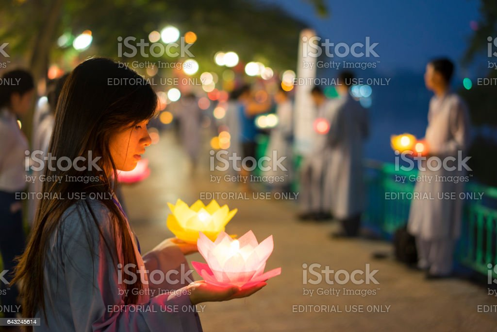 Hanoi, Vietnam - Oct 10, 2014: Buddhists hold flower garlands and colored lanterns for celebrating Buddha's birthday organised at Tran Quoc temple stock photo