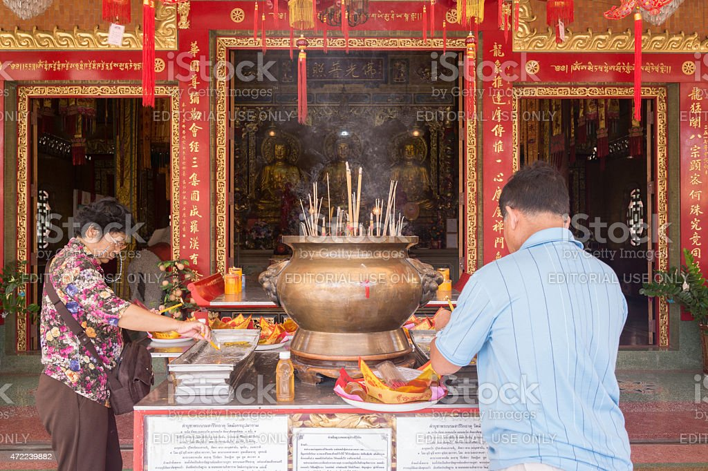 Buddhists lighting up candles and joss sticks in Chinese temple stock photo
