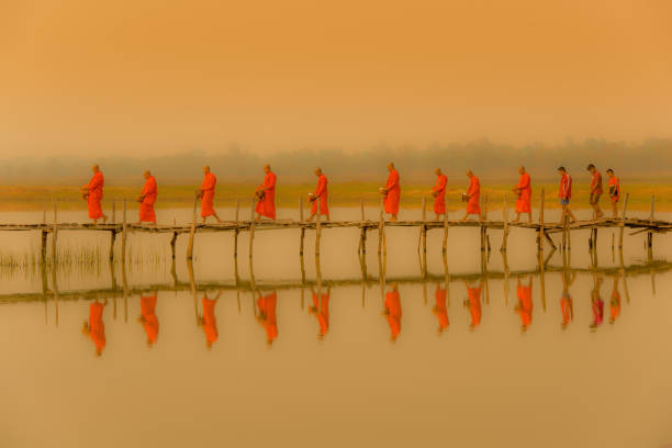 Buddist monks marching to seek alms in morning with fofoggy environment stock photo