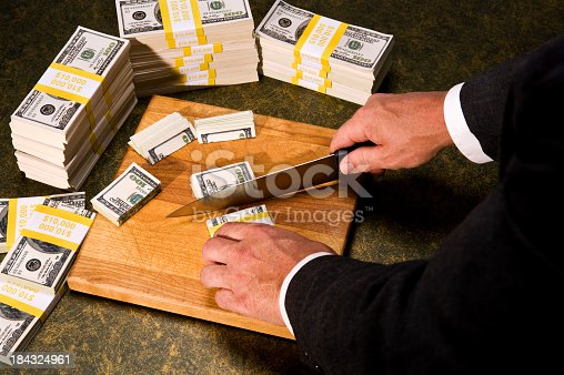 Budget Cutting - A politician trimming stacks of $100 bills with a Knife