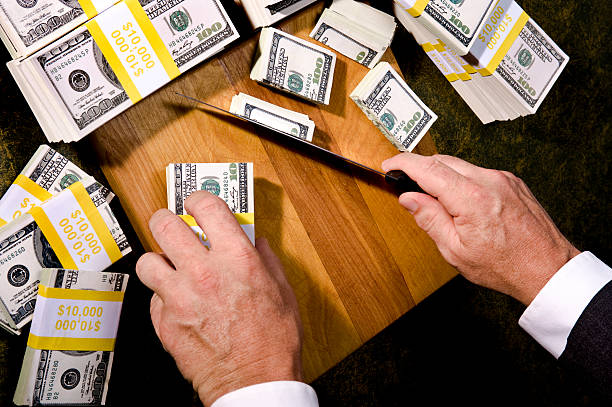 Budget Cutting, Congressman trimming stack of money Budget Cutting - A Businessman or Congressman cutting stacks of $100 bills with a Knife and cutting board debt ceiling stock pictures, royalty-free photos & images