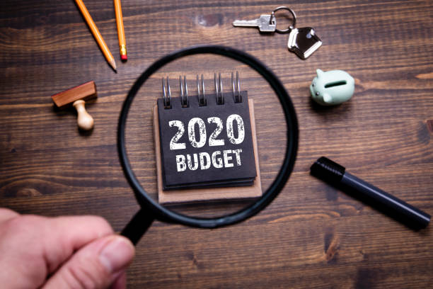 2020 Budget, family finances, economics, trade and career concept 2020 Budget, family finances, economics, trade and career concept. Man's hand, holding magnifying glass modern period stock pictures, royalty-free photos & images