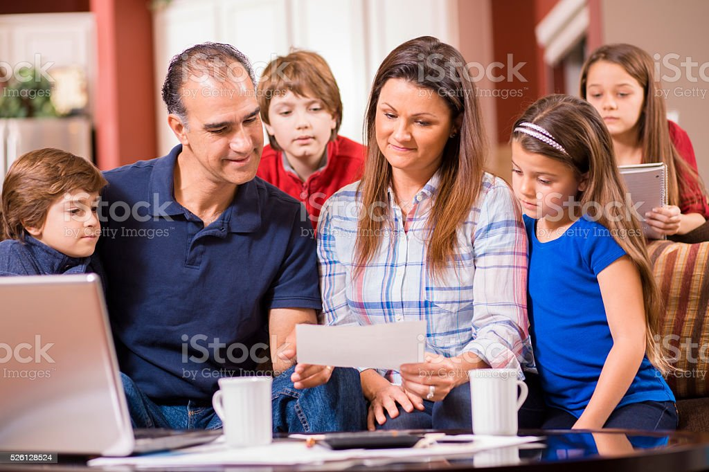 Budget.  Family of six together at home.  Mixed races. stock photo