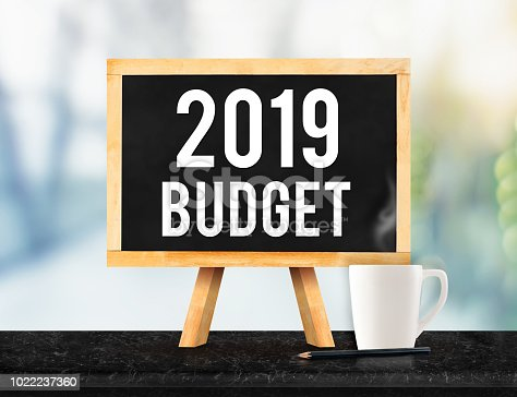 istock 2019 budget on blackboard with easel on black marble table with coffee cup and pencil on blurred office building New year business plan concept 1022237360