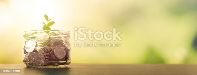 istock Budget, saving money with growing plant from jar 1084196984