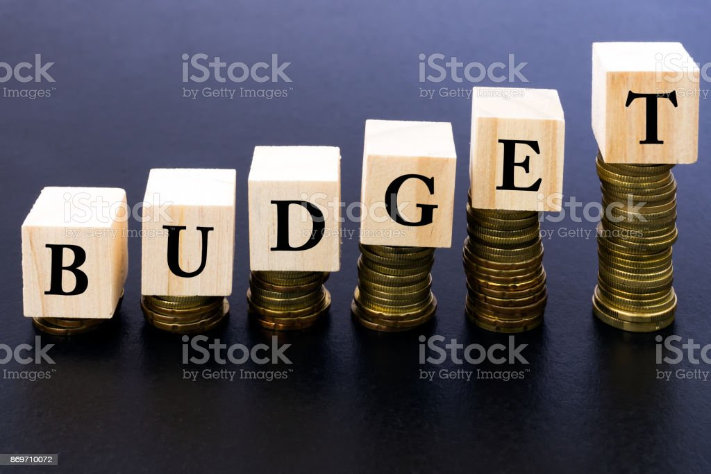 Budget Word on Wood Block on Top of Coins Stack. stock photo