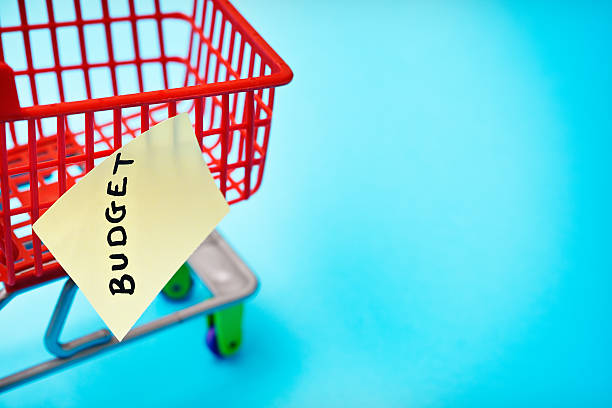 BUDGETsays label on miniature shopping cart; watch the costs! stock photo