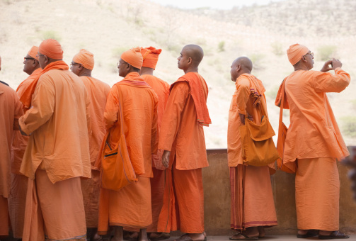 Jaipur, India - March 18, 2014: A group of Indian buddhist monks on vacation are visiting and taking photos in Amber Fort. Anyone who has camera sees different than others.
