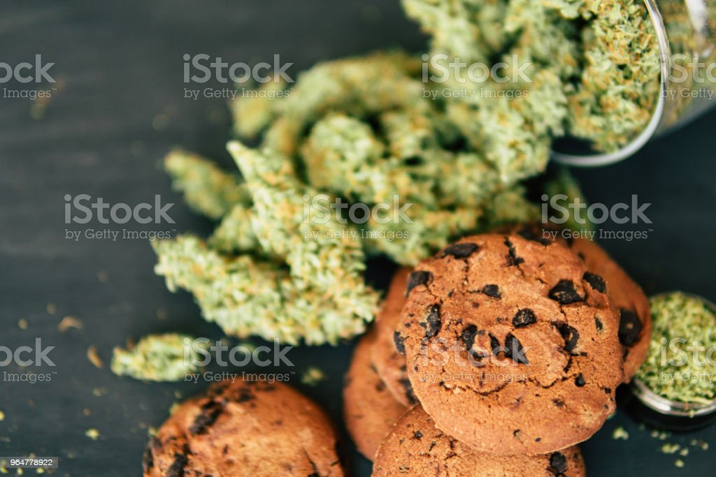 buds of marijuana on the table. Cookies with cannabis. Concept of cooking with cannabis herb. Treatment of medical marijuana for use in food, On a black background royalty-free stock photo