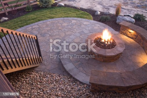 Circular fire pit at dusk on a flagstone patio