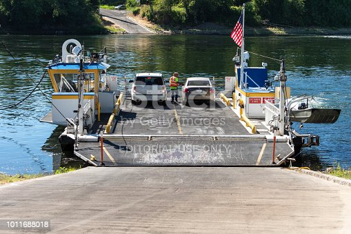 Independence, Oregon, USA - July 31, 2018: The Buena Vista Ferry at ramp ready to cross the Willamette River. This cable ferry travels between Marion County and Polk County. The ferry pilot can be seen collecting the river crossing fee. This is near Salem, the state capital.