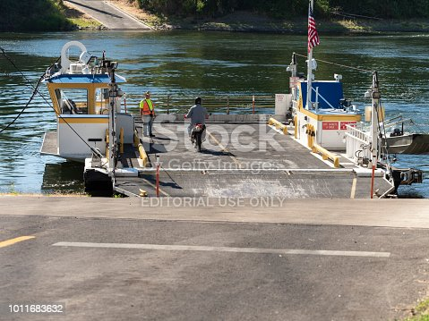 Independence, Oregon, USA - July 31, 2018: The Buena Vista Ferry at ramp ready to cross the Willamette River. A motorcycle rider is boarding by the ferry pilot. This cable ferry travels between Marion County and Polk County. This is near Salem, the state capital.