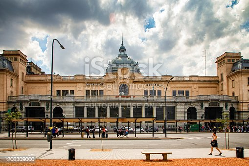 Buenos Aires Retiro Train station facade with a bus stop and a woman walking in the foreground.