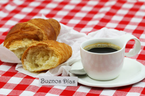 Buenos Dias (Good morning in Spanish) card with cup of coffee and croissant on checkered cloth stock photo