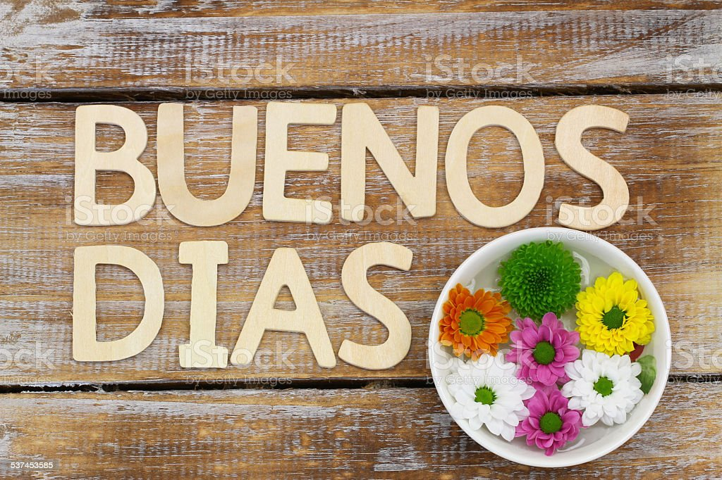 Buenos Dias (Good morning in Spanish) in wooden letters, flowers stock photo