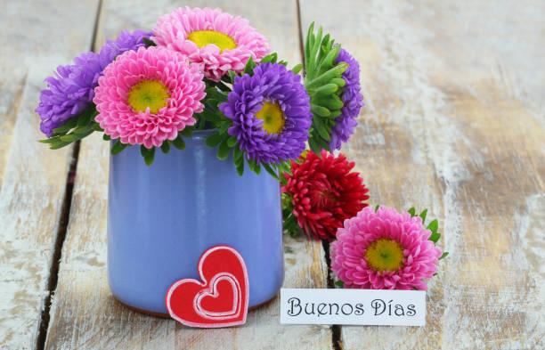 Buenos Dias (good morning in Spanish) with colorful daisy bouquet in blue vase on rustic wooden surface stock photo
