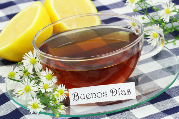 Buenos dias (which means good morning in Spanish) with cup of chamomile tea and fresh chamomile flowers stock photo