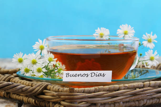 Buenos dias (which means Good morning in Spanish) with cup of chamomile tea on blue background stock photo