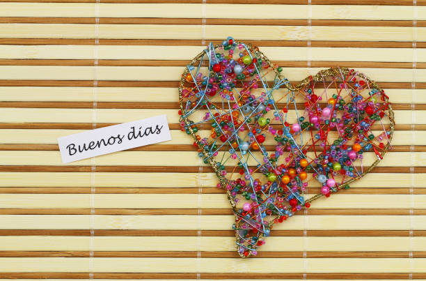 Buenos Dias (which means Good morning in Spanish) with heart made of colorful beads on bamboo mat stock photo