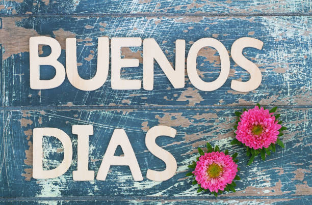 Buenos dias (which means good morning in Spanish) written with wooden letters and pink daisies stock photo