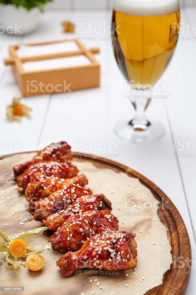 Buffalo chicken wings fried in sauce with glass of beer stock photo