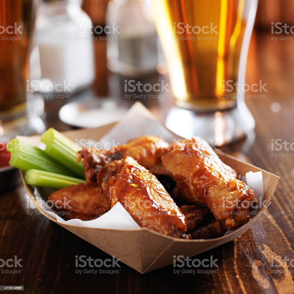buffalo chicken wings in basket with beer stock photo