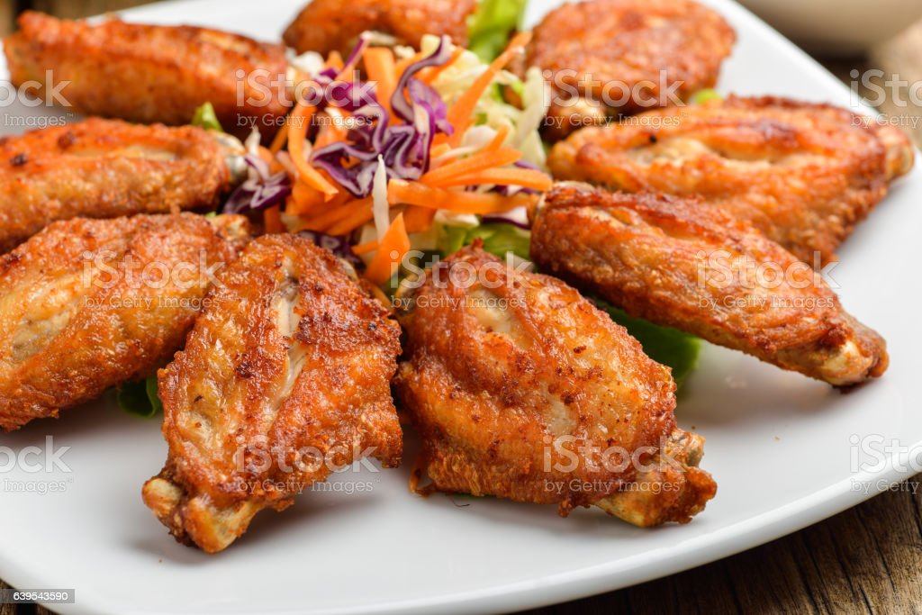 Buffalo chicken wings on white plate wooden background stock photo
