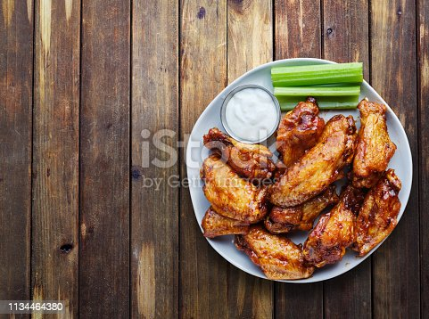 buffalo chicken wings with ranch and celery in overhead composition including copy space on wooden rustic table top