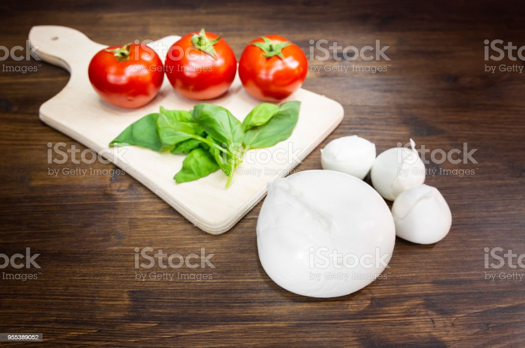 Buffalo mozzarella, tomatoes and basil, a typical combination known as Caprese, which is part of the Mediterranean diet. - Zbiór zdjęć royalty-free (Bazylia)