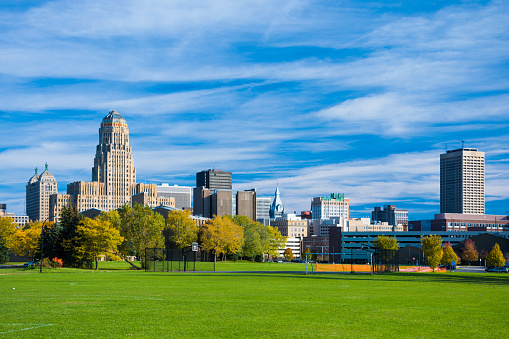 Downtown Buffalo skyline from a park during Autumn, with many clouds in the sky.  The building to the left is Buffalo City Hall.