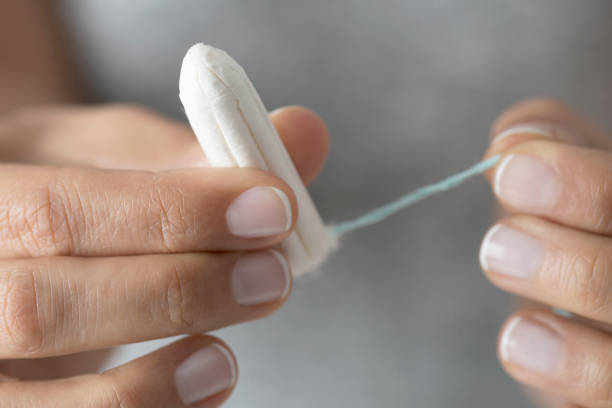 Tampon Close up of a woman's hands which are holding a tampon. tampon stock pictures, royalty-free photos & images
