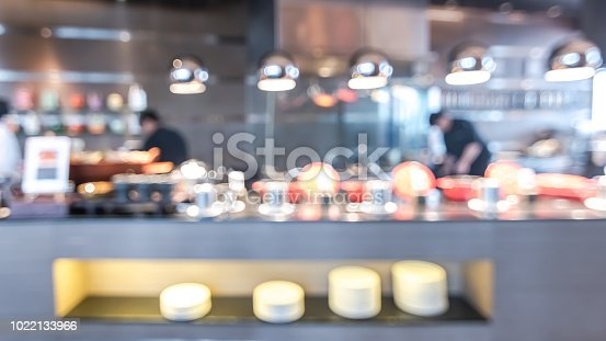 886308526istockphoto Buffet at hotel restaurant interior blur background with blurry open kitchen counter bar of food catering service business with chef staff cooking for breakfast, lunch or dinner meal 1022133966