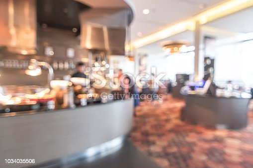 886308526istockphoto Buffet at hotel restaurant interior blur background with blurry open kitchen counter bar of food catering service business with chef staff cooking for breakfast, lunch or dinner meal 1034035506