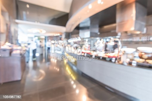 886308526istockphoto Buffet at hotel restaurant interior blur background with blurry open kitchen counter bar of food catering service business with chef staff cooking for breakfast, lunch or dinner meal 1054987782