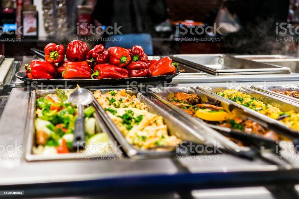 Buffet bar e bandejas com legumes assado salada, pimentão vermelho e pratos de carne - foto de acervo