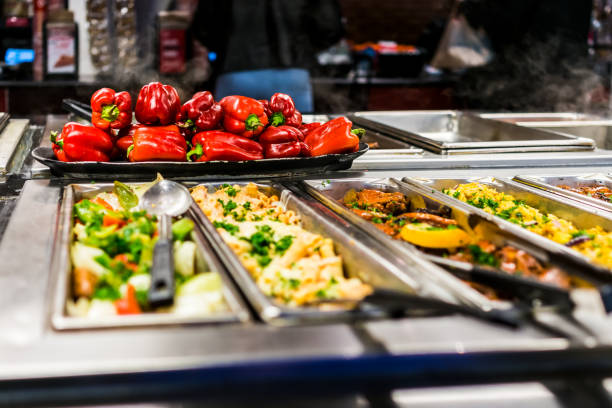 Buffet bar and trays with roasted salad vegetables, red bell peppers and meat dishes stock photo