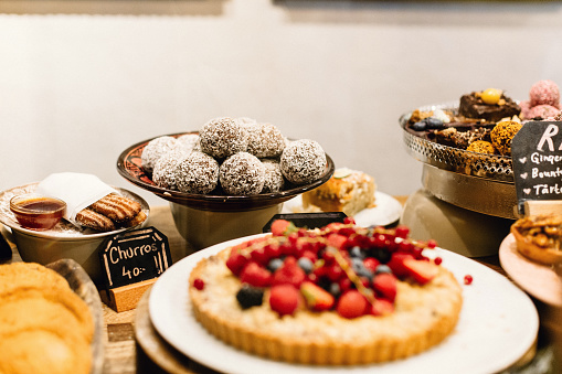 A display of vegan and vegetarian desserts and pastries on a table at a restaurant in Stockholm, Sweden