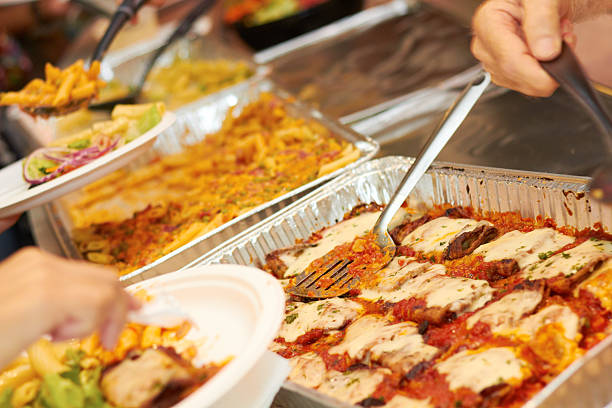 Buffet full of catered food with people serving themselves stock photo