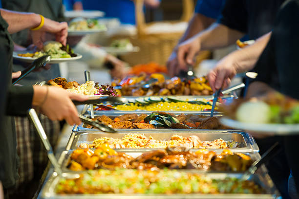 Buffet Line People getting food off a buffet line buffet stock pictures, royalty-free photos & images