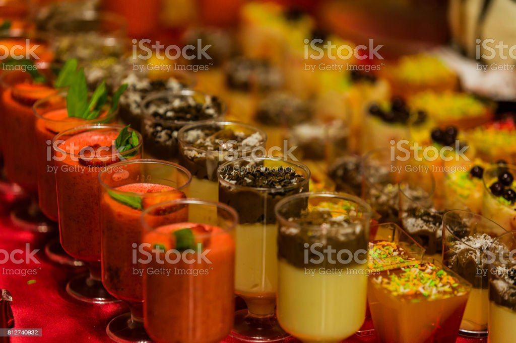 Buffet mousse dessert in a little glass topped with chocolate chips. Dessert canape. Strawberry mousse stock photo