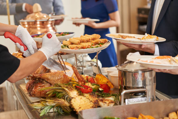 Buffet Cropped imaged of waiter cutting turkey for guests buffet stock pictures, royalty-free photos & images