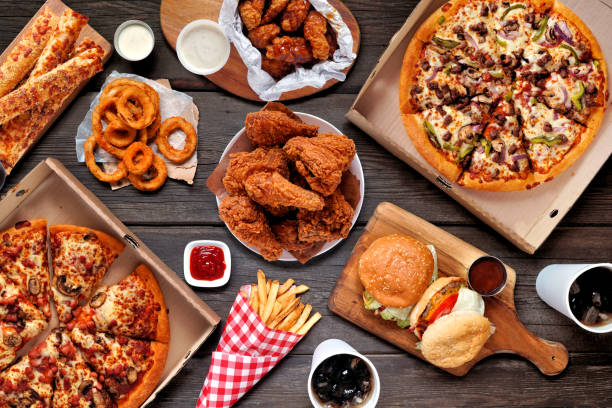 Buffet table scene of take out or delivery foods, above view over dark wood stock photo