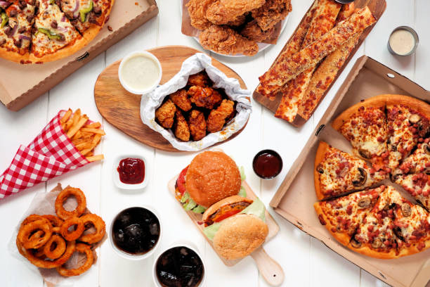 Buffet table scene of take out or delivery foods, top view over white wood stock photo