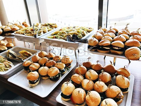 istock Buffet table with small hamburgers, sandwiches and vegetables. Catering service at the corporate business party or meeting 1129667976
